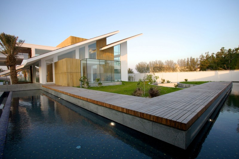 L-shaped-swimming-pool-around-the-house-with-wooden-deck-and-small-garden